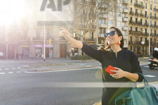 Woman hailing a taxi in the city