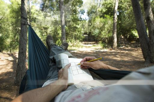 Man lying in hammock in the woods relaxing with puzzle book, partial view