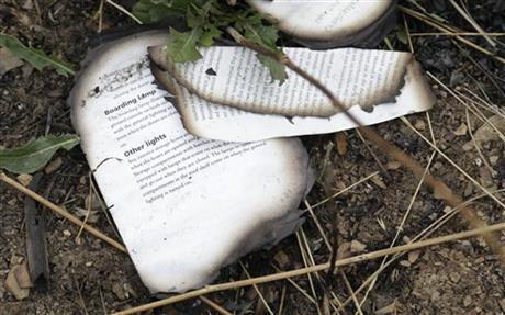 A burned book from the Malaysia Airlines Flight 17 plane is seen near village of Hrabove, eastern Ukraine, Tuesday, Sept. 9, 2014. (AP Photo/Sergei Grits)
