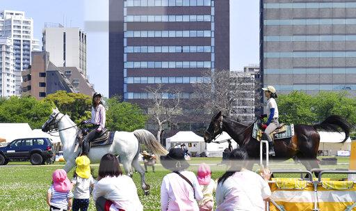 Horse riding adjacent to urban area in Fukuoka, Japan