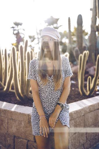 Attractive young woman wearing leopard print dress at cactus garden