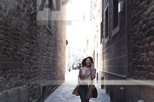Happy woman talking on cell phone in an alley