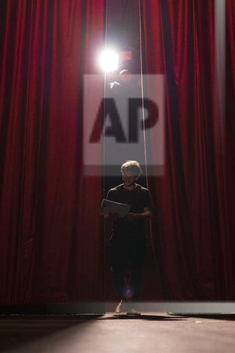 Barefoot actor walking on stage of theatre studying script
