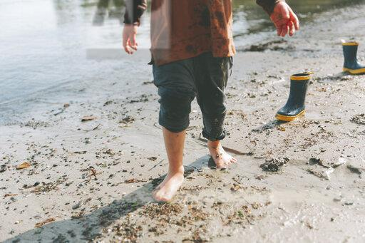 Boy playing on a the beach, walking barefoot in the mud