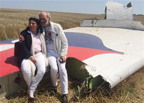 Jerzy Dyczynski and Angela Rudhart-Dyczynski whose daughter, 25-year-old Fatima, was a passenger on Malaysia Airlines flight MH17, sit on part of the wreckage of the crashed aircraft in Hrabove, Ukraine, Saturday, July 26, 2014. The couple who live in Perth, Australia, crossed territory held by pro-Russian rebels to reach the wreckage-strewn farm fields outside the village of Hrabove. They last spoke to Fatima shortly before she boarded the flight for Kuala Lumpur in Amsterdam on July 17. Rudhart-Dyczynski said,