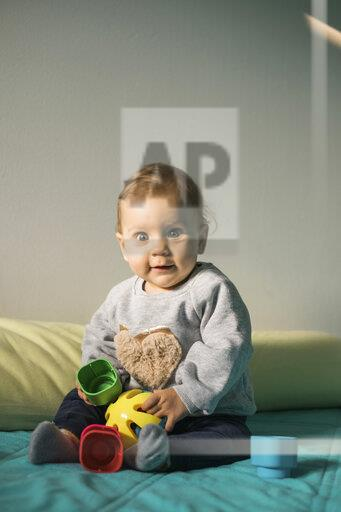 Portrait of baby girl sitting on bed playing with plastic toy