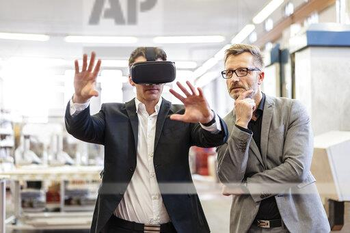 Two businessmen with VR glasses in factory