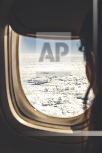 Argentina, Santa Fe, Rosario, woman looking through plane window