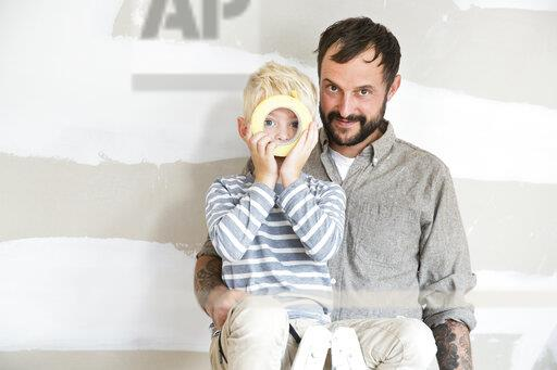 Portrait of father and son with sticky tape working on loft conversion