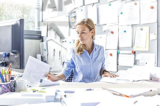 Woman sitting at desk in office doing paperwork