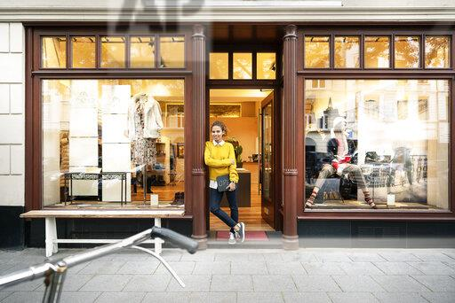 Young woman standing in door of a fashion store, holding laptop