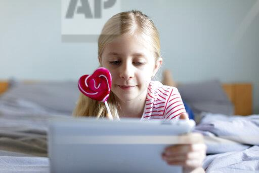 Portrait of blond girl lying on bed with lollipop using digital tablet