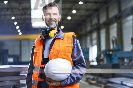 Portrait of smiling man wearing protective workwear in factory