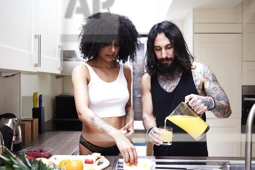 Young couple preparing healthy meal in kitchen