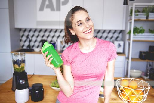 Portrait of smiling young woman with plastic cup preparing smoothie in the kitchen