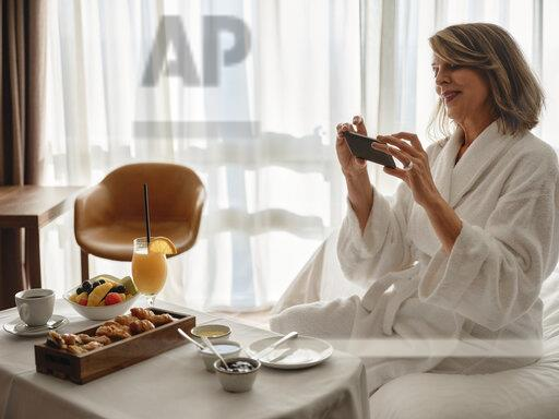Smiling blond elderly woman photographing breakfast through smart phone while sitting on bed in hotel room