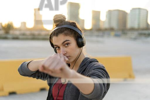 Sportive young woman with headphones during workout, boxing