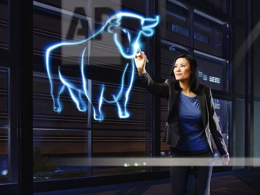 Businesswoman painting a bull with light