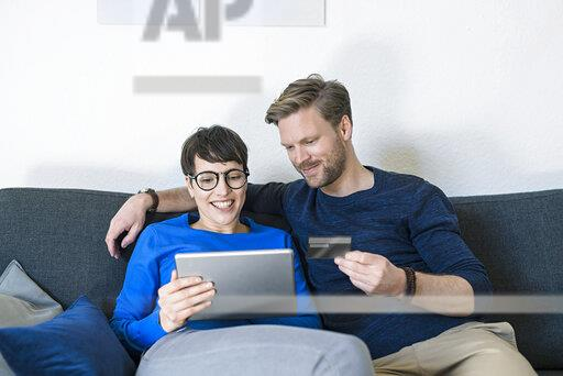 Happy casual couple relaxing on couch using tablet and holding credit card