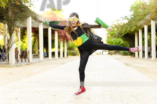 Girl in super heroine costume jumping