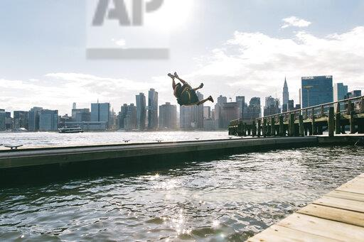 USA, New York, Brooklyn, two young men doing backflip on pier in front of Manhattan skyline