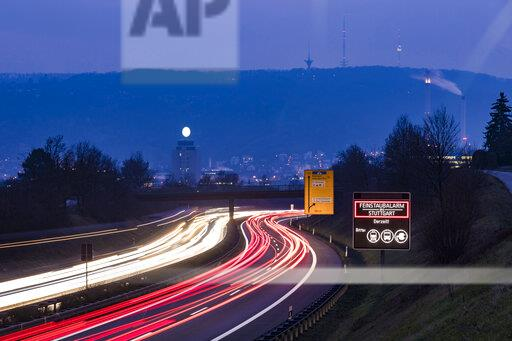 Germany, Stuttgart, Warning sign for particulate pollution alert and traffic in the evening