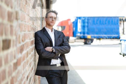 Businessman leaning against brick wall