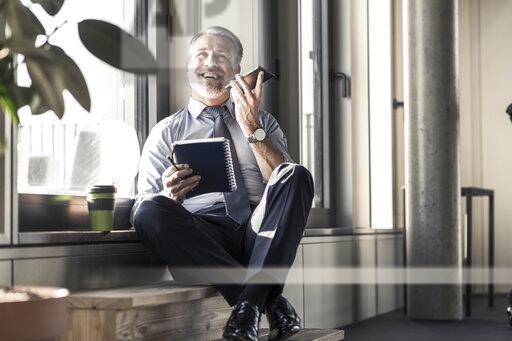 Happy mature businessman with notebook sitting at the window using cell phone