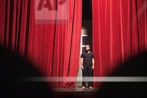 Barefoot actor standing on theatre stage
