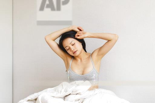 Young woman in bed waking up