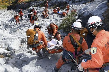 In this Sunday, Sept. 28, 2014 photo released by Tokyo Fire Department, Tokyo Fire Department firefighters carry an injured by Saturday's initial eruption from the summit of Mount Ontake in central Japan. A dozen more bodies were found Wednesday, Oct. 1 near the ash-covered summit of the Japanese volcano as searches resumed amid concern of toxic gasses and another eruption. (AP Photo/Tokyo Fire Department)