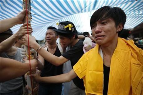 Student protesters are overwhelmed with emotions as they hold onto their tent while being threatened by residents and pro-Beijing supporters in Kowloon's crowded Mong Kok district, Friday, Oct. 3, 2014 in Hong Kong.