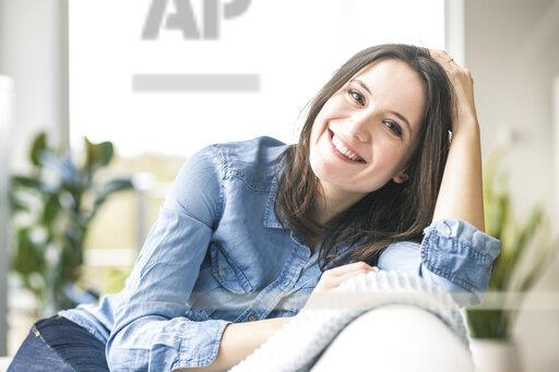 Portrait of happy woman sitting on the couch at home