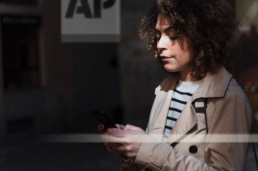Woman using cell phone in an alley