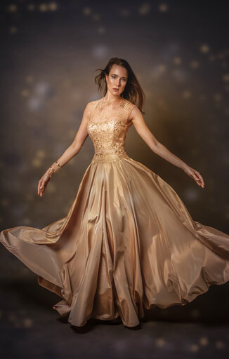 Portrait of young woman wearing golden evening dress