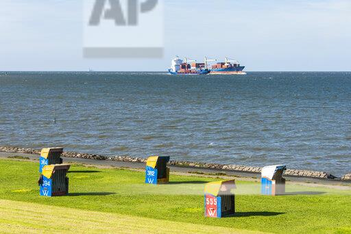 Germany, Cuxhaven, huge cargo boats passing the beach with beach chairs