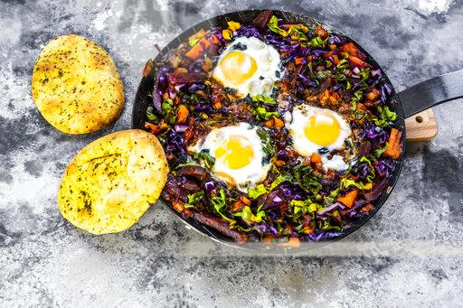 Pan of beetrootshakshoukawith chard, carrots, tomatoes, red cabbage and pita bread