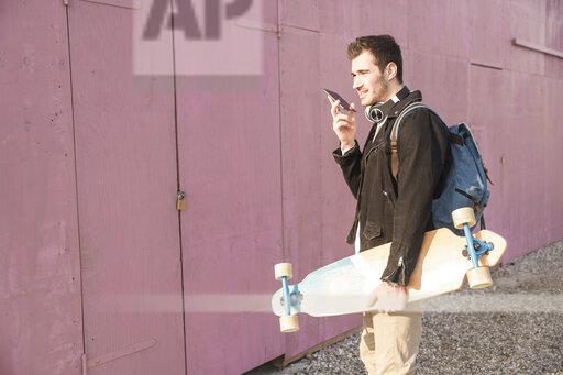 Young man with skatebaord and cell phone on the move
