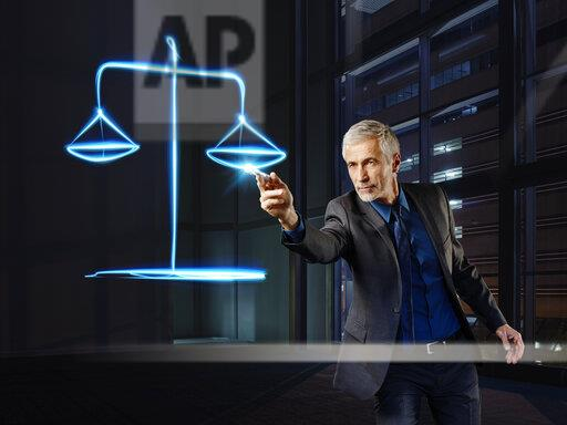 Businessman painting scales with light