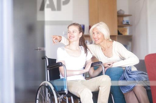 Mother with daughter in a wheelchair, pointing finger