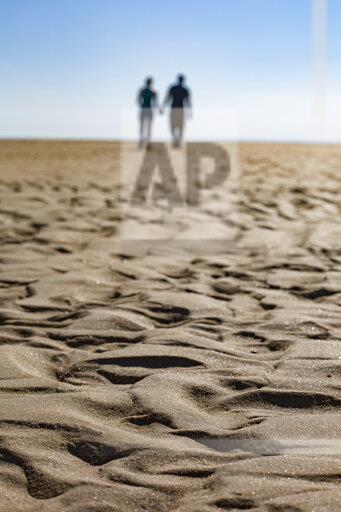 Wave pattern on the beach with silhouette of couple walking hand in hand in the background
