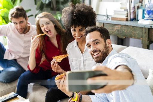 Freinds having fun, eating pizza together, taking selgies