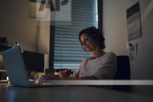 Businesswoman working overtime, using laptop, drinking coffee