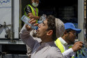 A Muslim pilgrim drinks water distributed by Saudi volunteers near the Grand Mosque, ahead of the annual Hajj pilgrimage, in the Muslim holy city of Mecca, Saudi Arabia, Muslim holy city of Mecca, Saudi Arabia, Saturday, Aug. 18, 2018. The annual Islamic pilgrimage draws millions of visitors each year, making it the largest yearly gathering of people in the world. (AP Photo/Dar Yasin)