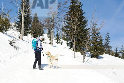 Germany, Bavarian Forest, Lusen, smiling woman with dog hiking in winter