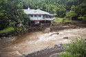 A home on Kahekili Highway near the Waihee River Bridge, was evacuated after a flash flood breached the property on Wednesday afternoon, Sept. 12, 2018, in Maui, Hawaii. Maui County says several homes on Maui are being evacuated because of floodwaters from Tropical Storm Olivia. (Cindy Ellen Russell/Honolulu Star-Advertiser via AP)