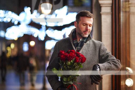 Portrait of waiting man with bunch of red roses checking the time
