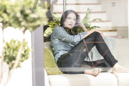 Pensive woman sitting on couch behind windowpane at home