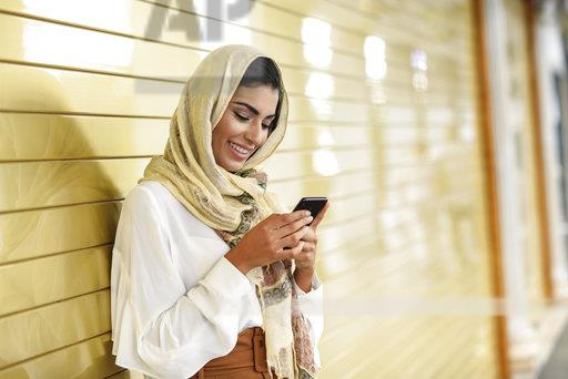 Spain, Granada, young Arab tourist woman wearing hijab, using smartphone