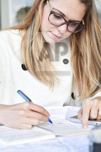 Young blond freelancer taking notes